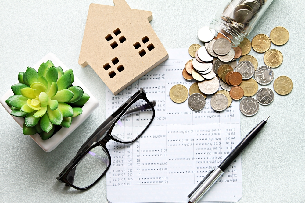Business, finance, saving money, property ladder or mortgage loan concept : Wood house model, coins and financial statement or saving account book on desk table, cap rate