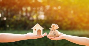 Loans for real estate concept, a man and a women hand holding a money bag and a model home put together in the public park., Investment Lending, Real Estate Investment